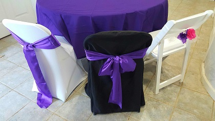 left white spandex chair cover with a purple satin sash
